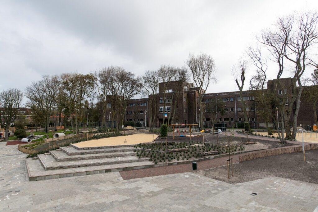 Het schoolplein van OBS Het Volle Leven na de aanleg van het groenblauwe schoolplein. Je ziet veel hoogte verschillen, zand, en groen.