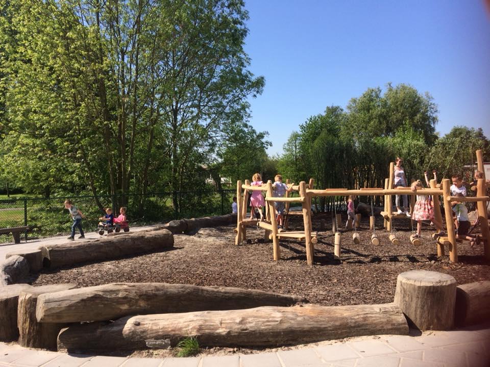 Op het nieuwe plein, na de aanleg, een waterdoorlatende ondergrond door gebruik van boomschors en het gebruik van natuurlijke materialen en speeltoestellen.